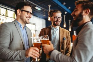 Business people drink beer after work in pub. Businessmen enjoy a beer