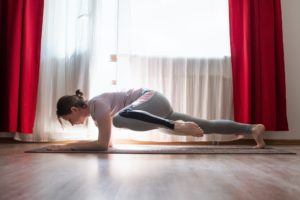 Woman doing push ups exercises for training chest and arms muscles at home
