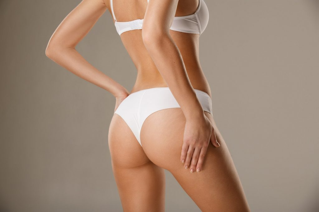 Woman pinching her skin on hips testing subcutaneous body fat layer